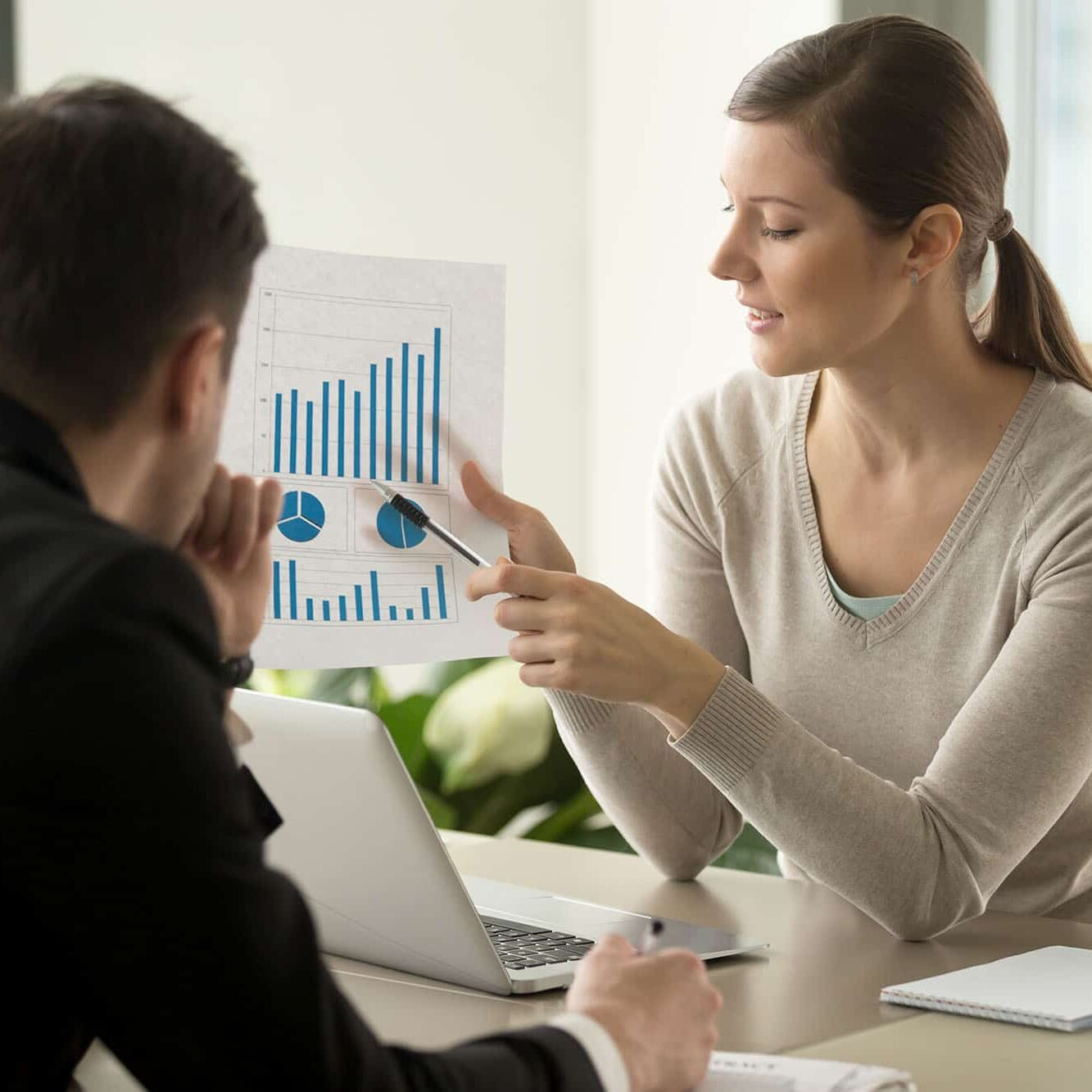 Attractive millennial businesswoman presenting company financial indicators, telling business partner about investment plan, showing document with project positive stats sitting at office desk